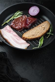 Сырая говяжья печень, нарезанная беконом на сковороде для гриля