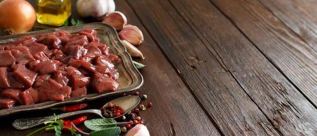 木製のテーブルにスパイス、ハーブ、野菜と生の牛レバー