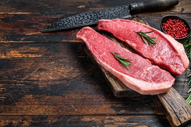 まな板の上に生の牛肉のキャップサーロインステーキ。暗い木の背景。上面図。スペースをコピーします。