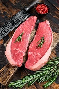 まな板の上に生の牛肉のキャップサーロインステーキ。暗い木の背景。上面図。