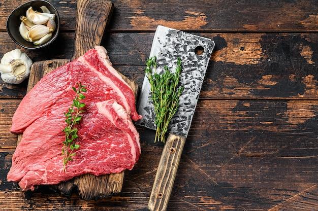 Стейк крупицы отбивной сырого мяса говядины на разделочной доске. темный деревянный фон. вид сверху. скопируйте пространство.