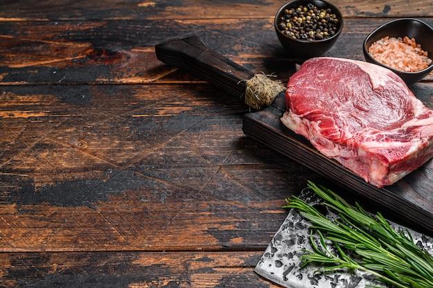 生の牛肉クラブまたは骨ステーキのサーロイン。ダークウッドのテーブル。上面図。