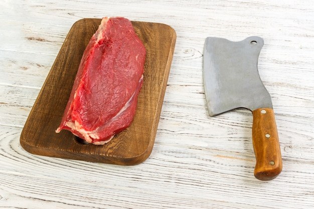 Raw beef meat on cutting board with old vintage cleaver