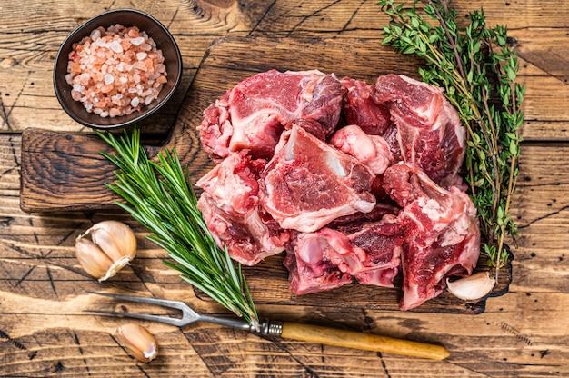 Сырое мясо говядины, нарезанное кубиками для тушения с косточкой. деревянный