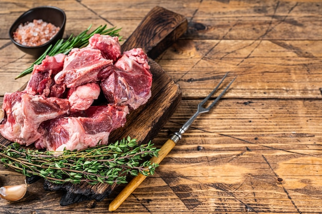 Raw beef  meat diced for stew with bone. wooden background. top view. copy space.
