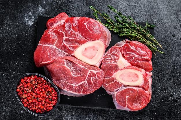 원시 쇠고기 고기 오소 부코 생크 스테이크, 이탈리아 오소부코. 검은 배경. 평면도.