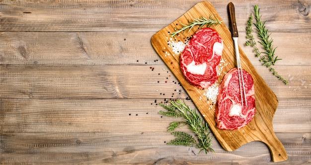 나무 주방 책상에 허브와 향신료를 곁들인 생 쇠고기 립 아이 스테이크. 음식 배경