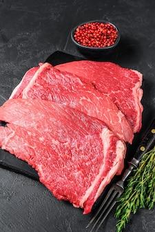 大理石のボードに生の牛肉のモモステーキ。上面図。
