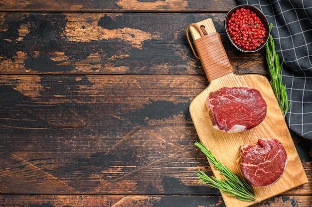 Стейк из сырого говяжьего мяса филе вырезки на разделочной доске.