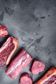 Набор стейков из сырого говяжьего мяса, томагавк, кость, стейк, ребрышки и вырезки, на сером каменном фоне, плоская планировка, вид сверху, с местом для текста
