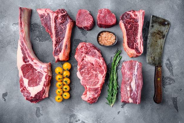 Набор стейков из сырого говяжьего мяса, томагавк, кость, клубный стейк, ребрышки и вырезки, на сером каменном фоне, плоская планировка, вид сверху