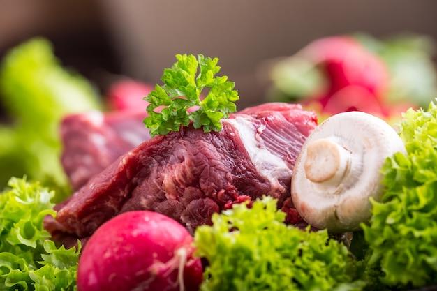 신선한 야채와 함께 원시 쇠고기 고기입니다. 양상추 샐러드 무와 버섯에 얇게 썬 쇠고기 스테이크.