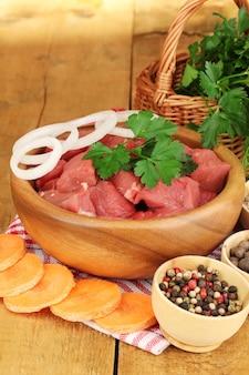 木製のテーブルにハーブとスパイスと生の牛肉