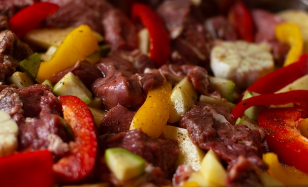 Raw beef meat with raw vegetables: zucchini, garlic, red and yellow pepper with natural spices and herb