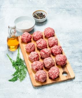 소박한 테이블에 향신료와 향기로운 딜과 원시 쇠고기 미트볼.