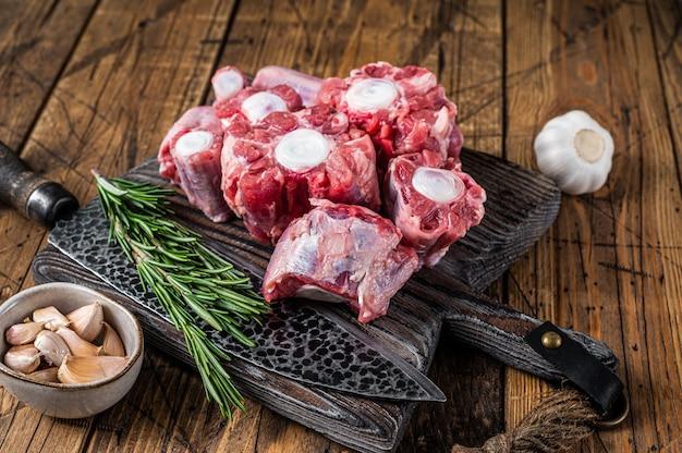 원시 쇠고기 oxtail 칼으로 나무 커팅 보드에 고기를 잘라. 나무 배경입니다. 평면도.