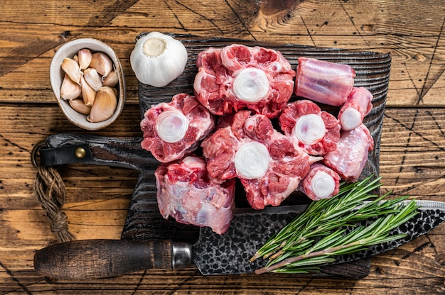 Сырая говядина нарезать мясо из бычьего хвоста на деревянной разделочной доске с ножом