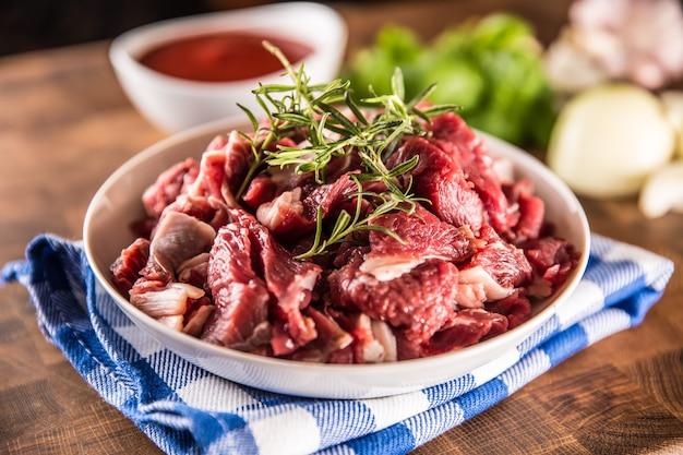 정육점 보드에 그릇에 로즈마리와 원시 쇠고기 조각.