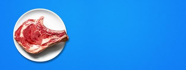 원시 쇠고기 프라임 갈비와 접시 파란색 배경에 고립. 평면도. 가로 배너