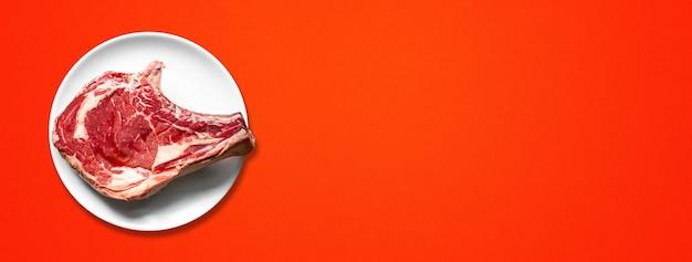 원시 쇠고기 프라임 갈비와 접시 빨간색 배경에 고립. 평면도. 가로 배너