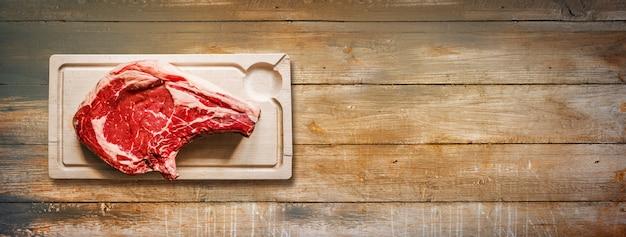 원시 쇠고기 프라임 갈비와 오래 된 나무 배경에 고립 된 나무 커팅 보드. 평면도. 가로 배너
