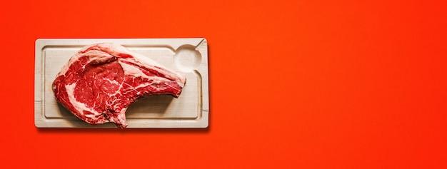 원시 쇠고기 프라임 갈비와 붉은 배경에 고립 된 나무 커팅 보드. 평면도. 가로 배너