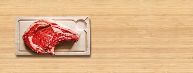 원시 쇠고기 프라임 갈비와 나무 배경에 고립 된 나무 커팅 보드. 평면도. 가로 배너