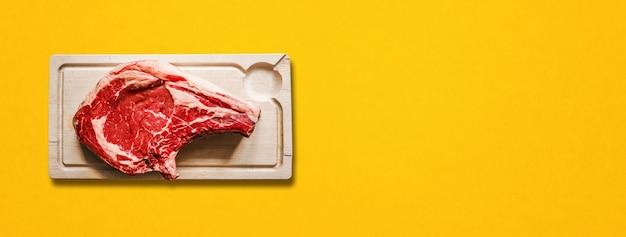 노란색 배경에 분리된 원시 쇠고기 프라임 립과 나무 커팅 보드. 평면도. 가로 배너