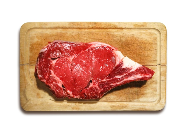 Raw beef prime rib  on a cutting board isolated on white background