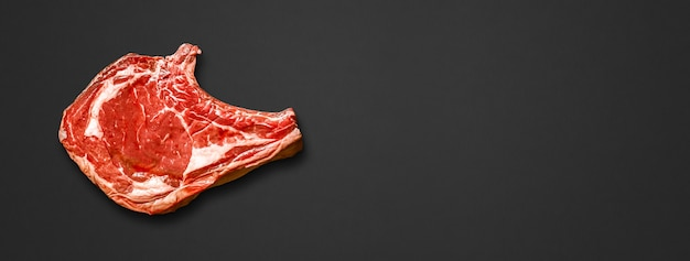 Raw beef prime rib isolated on black background. top view. horizontal banner