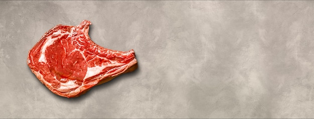 Raw beef prime rib isolated on light concrete background. top view. horizontal banner
