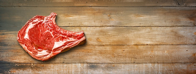 Raw beef prime rib isolated on old wooden background. top view. horizontal banner