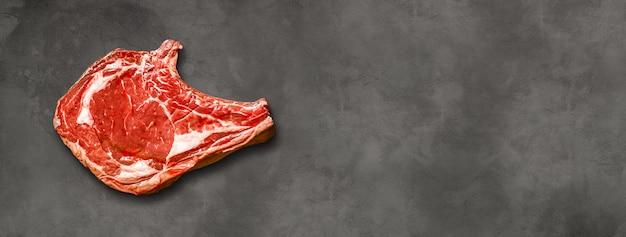 Первичное ребро сырой говядины, изолированные на темном фоне бетона. вид сверху. горизонтальный баннер