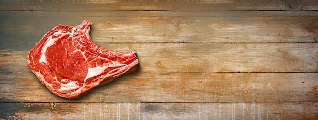 원시 쇠고기 프라임 립 오래 된 나무 배경에 고립입니다. 평면도. 가로 배너