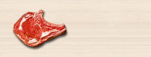 木製の背景に分離された生の牛肉プライムリブ。上面図。横バナー