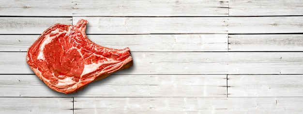 Raw beef prime rib isolated on white wooden background. top view. horizontal banner