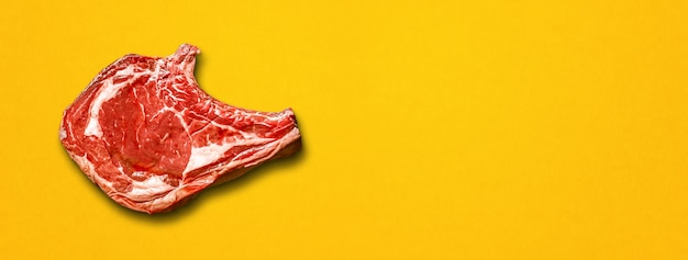 Raw beef prime rib isolated on yellow background. top view. horizontal banner