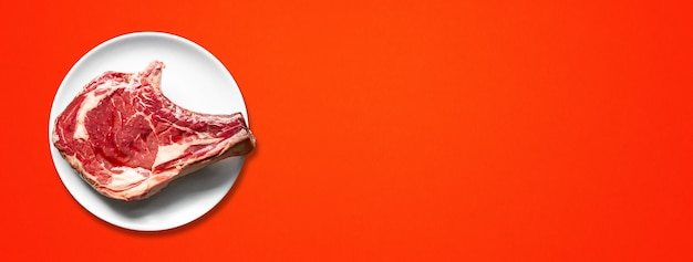Raw beef prime rib and plate isolated on red background. top view. horizontal banner