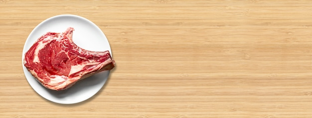 Raw beef prime rib and plate isolated on wooden background. top view. horizontal banner