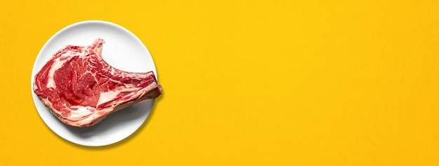Raw beef prime rib and plate isolated on yellow background. top view. horizontal banner