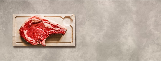 Raw beef prime rib and wooden cutting board isolated on light concrete background. top view. horizontal banner