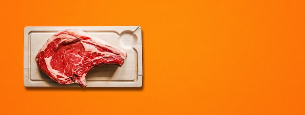 Raw beef prime rib and wooden cutting board isolated on orange background. top view. horizontal banner