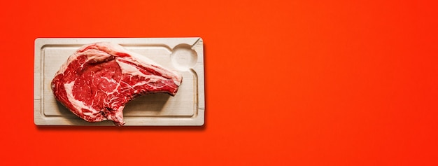 Raw beef prime rib and wooden cutting board isolated on red background. top view. horizontal banner