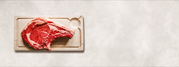 Raw beef prime rib and wooden cutting board isolated on white concrete background. top view. horizontal banner