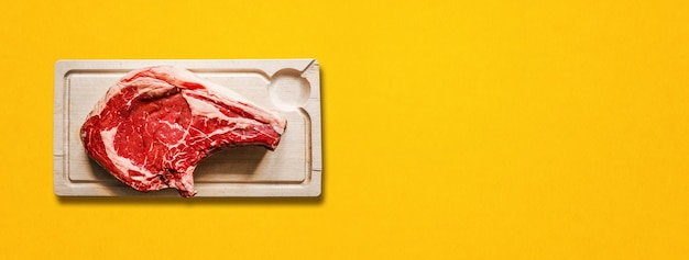 Raw beef prime rib and wooden cutting board isolated on yellow background. top view. horizontal banner