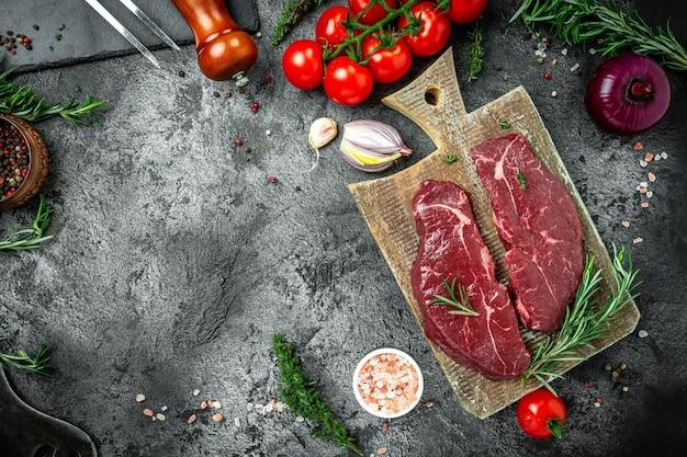Сырой стейк из говядины на вуденской доске. черный фон, свежие кусочки свинины, готовые к приготовлению, баннер, место рецепта меню для текста, вид сверху.