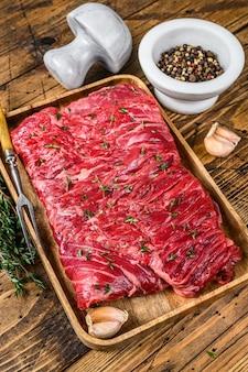 허브와 함께 나무 쟁반에 원시 쇠고기 라운드 컷 고기. 나무 배경입니다. 평면도.