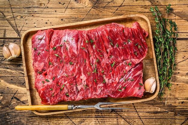 Сырое мясо говядины на деревянном подносе с зеленью