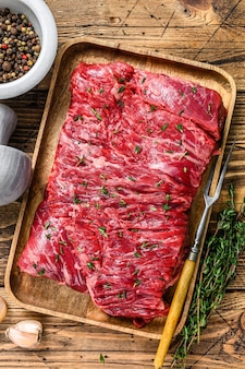 Raw beef round cut meat on a wooden tray with herbs