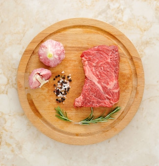 Raw beef on a round wooden board with garlic and spices